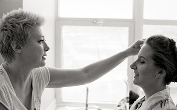 Nika Vaughan Bridal Artists makeup artist Lia Rivette applying makeup to bride