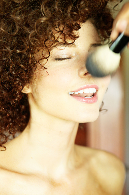 Bride with great smile and curly hair getting makeup service with powder brush
