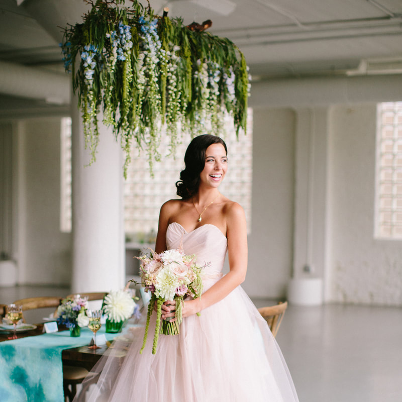 Smiling brunette bride with floral bouquet in front of bridal reception table and floral installation