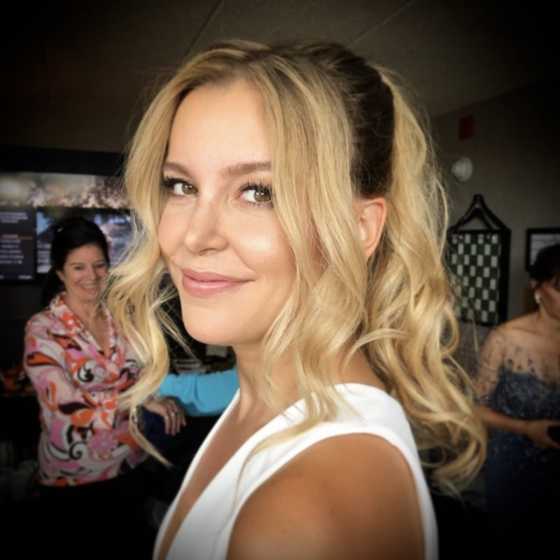 Blonde bride with lots of fringe and high ponytail with bridesmaids getting ready in background